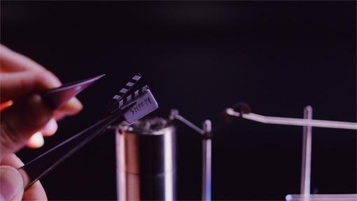 ピンセットでつまみまげられた極小サイズのカチンコで動画がスタート