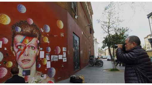 カメラでデヴィッド・ボウイの壁画を撮影する鋤田正義 / ©2018「SUKITA」パートナーズ
